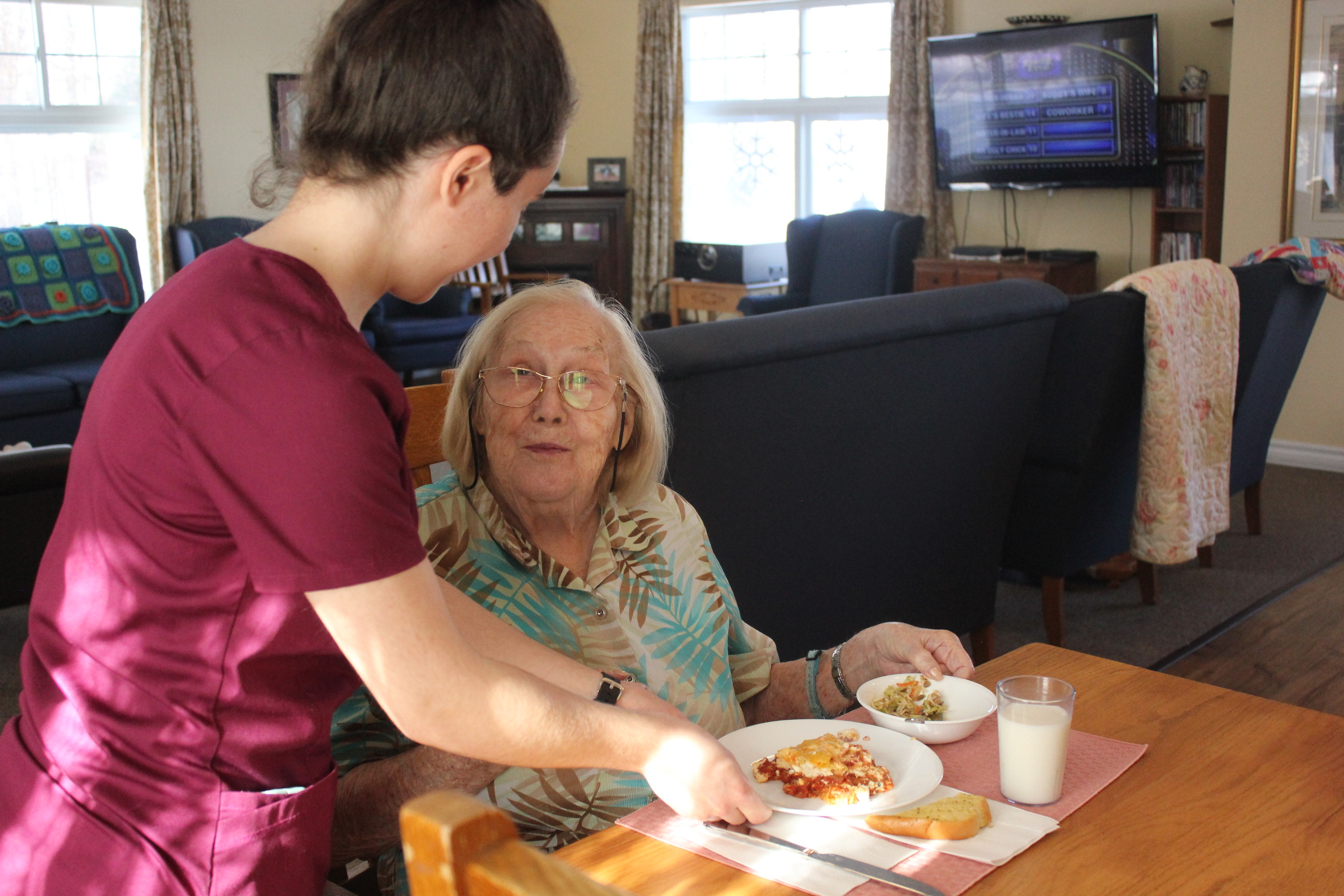 Richmond Care Home resident being served a healthy meal by staff.